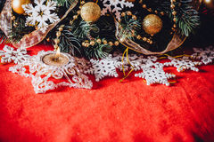 Christmas card with fir tree branch decorated with golden baubles, garlands and vintage snowflakes on a red background. Royalty Free Stock Photography
