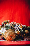 Christmas card with fir tree branch decorated with golden baubles, garlands and vintage snowflakes on a red background. Stock Photos