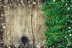 Christmas card of fir tree on rustic wooden background. Snow effect, copy space for text, vintage toning Stock Photography