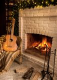 Christmas card. Fireplace with a bright flame and a garland scattered on the floor of firewood. Nearby is a guitar stock photos