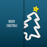 Christmas card with folded white paper tree on a blue background Royalty Free Stock Photos