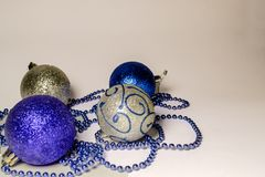 Four colored shiny Christmas balls lie on the left on a white background royalty free stock photo