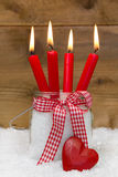 Christmas card: four red burning candles with bow and heart on s Stock Photography