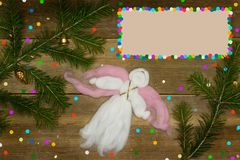 Christmas card with frame for text. One white woolen angel flying, colorful confetti and evergreen branches Royalty Free Stock Images