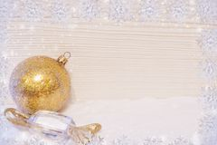 Framework of snowflakes, golden Christmas toys ball and candy are lying on snow, light wooden background and copy space. royalty free stock image
