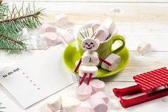 Christmas card with fun marshmallow snowman in green cup, tree Royalty Free Stock Photos