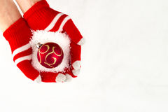 Christmas card, gloves on hands holding red ball with snowflakes Stock Photos