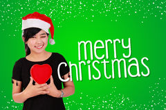 Christmas card on green background. Green Christmas card background design composition with image of nice smiling Asian girl holding a heart sign Stock Images