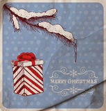 Christmas card. Hand-drawn fir branch covered with snow and icicle and gift on blue dotted  background with old wrinkled paper texture Stock Images