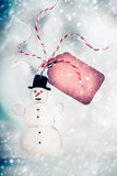 Christmas card with handmade snowman and tag on winter bokeh background Stock Photography