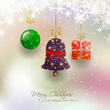 Christmas card with hanging bauble,gift box,bell on magical snowfall background Stock Images