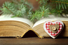 Christmas card: Heart-shaped ornament, Christmas berries and an old book Stock Photos