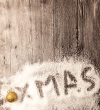 Christmas card with the inscription xmas golden balls in the snow on a wooden background. Royalty Free Stock Image