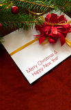 Christmas card or invitation with red envelope surrounded by decorations. Space for copy. Royalty Free Stock Photography