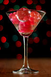 Christmas card: martini glass with balls on bokeh background Stock Images