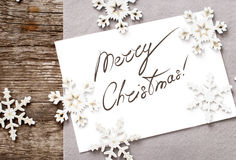 Christmas Card with Message Merry Christmas on the. Letter on white, decorated snowflakes stock image