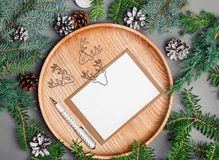 Christmas card mock-up on wooden plate with fir branches. And pine cones Stock Image