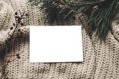 Christmas card mockup. empty christmas card with space for text, template on knitted sweater and fir branches. merry. Christmas, seasonal greetings, happy royalty free stock photography