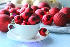 Christmas card, new year. Red balls for the Christmas tree poured into a white Cup . royalty free stock photo