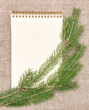 Christmas card with notebook and fir branch on burlap Stock Photography