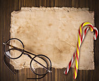 Christmas card. Old paper on a wooden background with Christmas sweets royalty free stock images