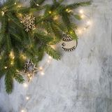 Christmas card at old vintage board with branches christmas tree, wooden snowflakes and balls and glowing lights. New Year stock image