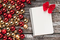 Christmas card. Old wood background, half full of baubles. And a notebook for a greeting message. Top view. Xmas card.  royalty free stock photo