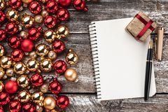 Christmas card. Old wood background, half full of baubles. And a notebook for a greeting message. Top view. Xmas card.  royalty free stock photos