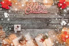 Christmas card, on old wooden background. Gifts and handmade toys. Space for text. Top view. Effect of lights and snow.  royalty free stock photos