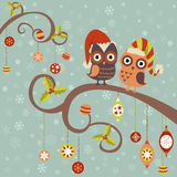 Christmas card of owls in hats. Cute winter Christmas card of owls in hats sitting on a tree branch with ball toys Royalty Free Stock Image