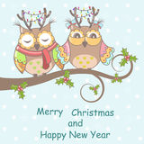 Christmas card with owls. On a tree on a blue background Stock Photo