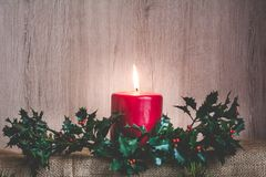 Christmas card with a place for your congratulations. Candle and branches of a holly on a wooden background. With a place for your greeting text Stock Images