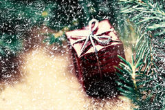 Christmas card with present box and fir cone tree on wooden back Stock Image