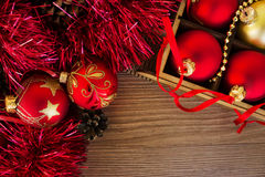 Christmas card with red and gold balls on the wooden table Stock Photos