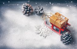 Christmas card with red sled, gift box, pine cones. Black background covered snow, space for text, retro style Stock Images