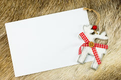 Christmas card with reindeer. White letter with wooden reindeer on reindeer-skin as background. No text Royalty Free Stock Photography