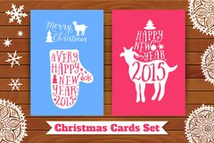 Christmas card set. Goat and mitten with lettering elements, on table top. Decorated with paper snowflakes. Royalty Free Stock Photos