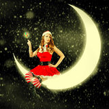 Christmas card. sexy woman in santa claus clothes. Christmas card. Young sexy beautiful woman in santa claus clothes sitting on a moon Royalty Free Stock Photo