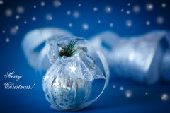 Christmas card with silver balls and ribbon. On a blue background stock photo