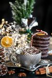 Christmas card silver cup of sweet cream on black table, with sweets, cinnamon, aniseed, winter cone, and empty glass royalty free stock photos