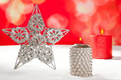 Christmas card of silver star and candle on snow Stock Image