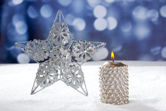 Christmas card of silver star and candle on snow Royalty Free Stock Images