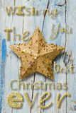 Christmas greeting with nice message. Christmas card. Simple Christmas greeting with nice message in letters of golden glitter and a star on blue wooden rustic royalty free stock photos