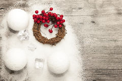 Christmas card with snowballs and snow and Christmas wreaths on the wooden background. Royalty Free Stock Images