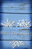 Christmas card with snowflakes on blue wooden background. Christmas card with snowflakes and greetings on vintage blue wooden background Stock Image
