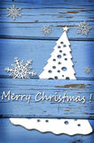 Christmas card with snowflakes and tree on blue wooden backgroun Royalty Free Stock Photo