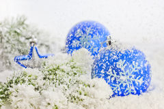 Christmas card it snows. Christmas branch of tree blue baubles against snow background royalty free stock photos