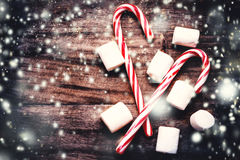 Christmas Card with  striped hard candy cane and marshmallows ov Royalty Free Stock Images