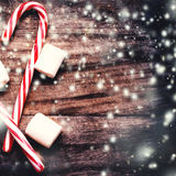Christmas Card with  striped hard candy cane and marshmallows ov Royalty Free Stock Image