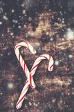 Christmas Card with  striped hard candy cane over wooden backgro Royalty Free Stock Photos